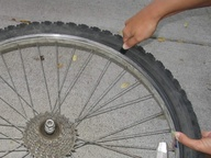 how to get a bike tire back on the rim